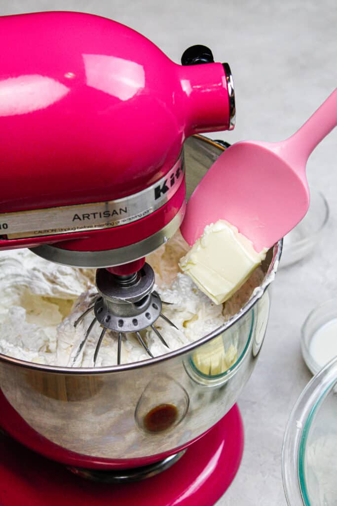 image of adding butter gradually into swiss meringue buttercream frosting