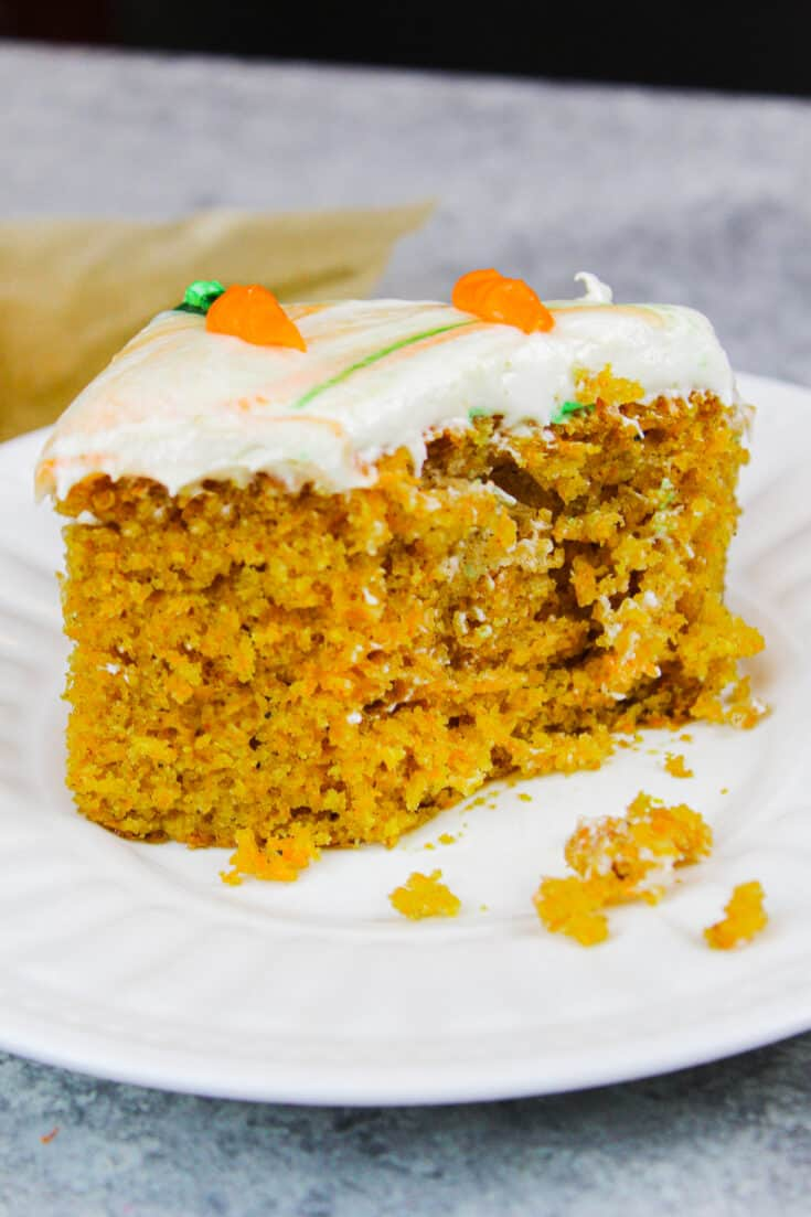 image of slice of carrot cake sheet cake with bit taken to show how moist the cake is