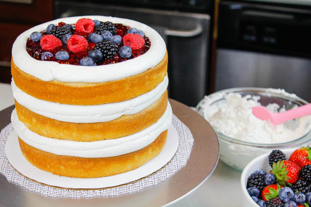 image of cake layers stacked with mixed berry filling and piped frosting dam of mascarpone cream cheese frosting