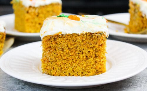 image of carrot cake sheet cake slice on a plate with others in the background