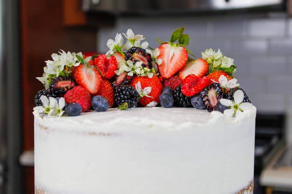 image of top of a cake decorated with fresh berries and edible flowers for spring and easter
