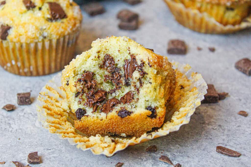 image of chocolate chip muffin that's been bitten into to show how fluffy and tender it is