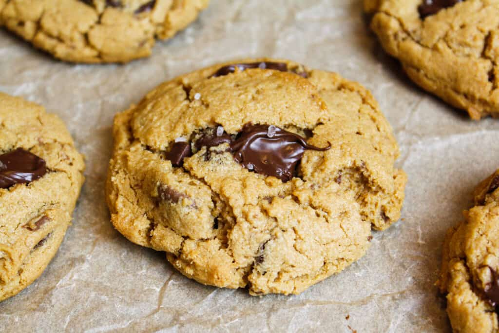 image of peanut butter chocolate chip cookie on parchment paper sprinkled with sea salt
