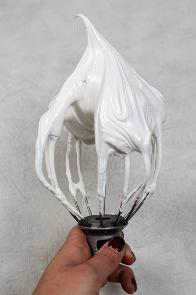 image of meringue made on a whisk attachment for swiss meringue frosting