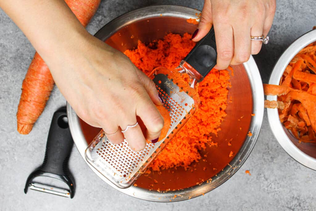 image of carrots being grated on a microplane grater for carrot cake recipe