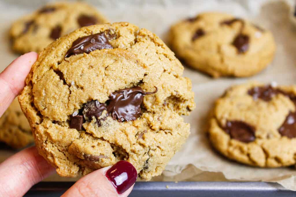 photo of flourless peanut butter cookie held in hand to show melting chocolate chips