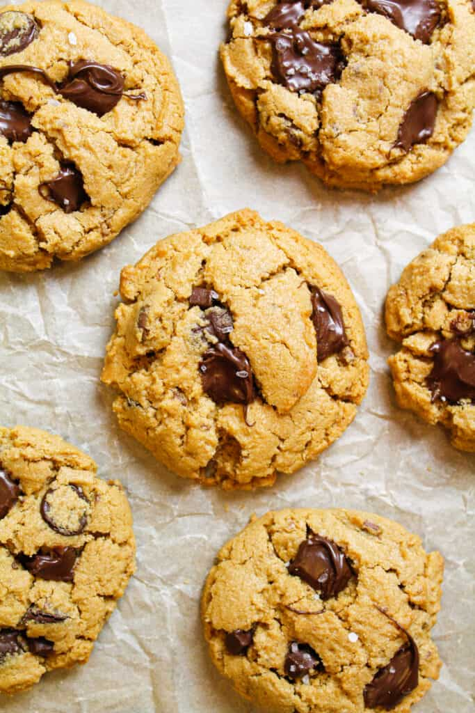 image of 5 Ingredient Peanut Butter Cookie held in hand to show melting chocolate and flakes of sea salt