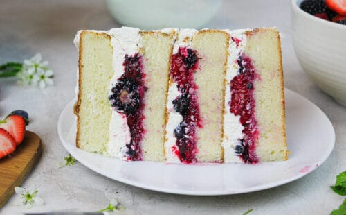 photo of a slice of berry chantilly cake showing mixed berry filling and fluffy mascarpone cream cheese frosting