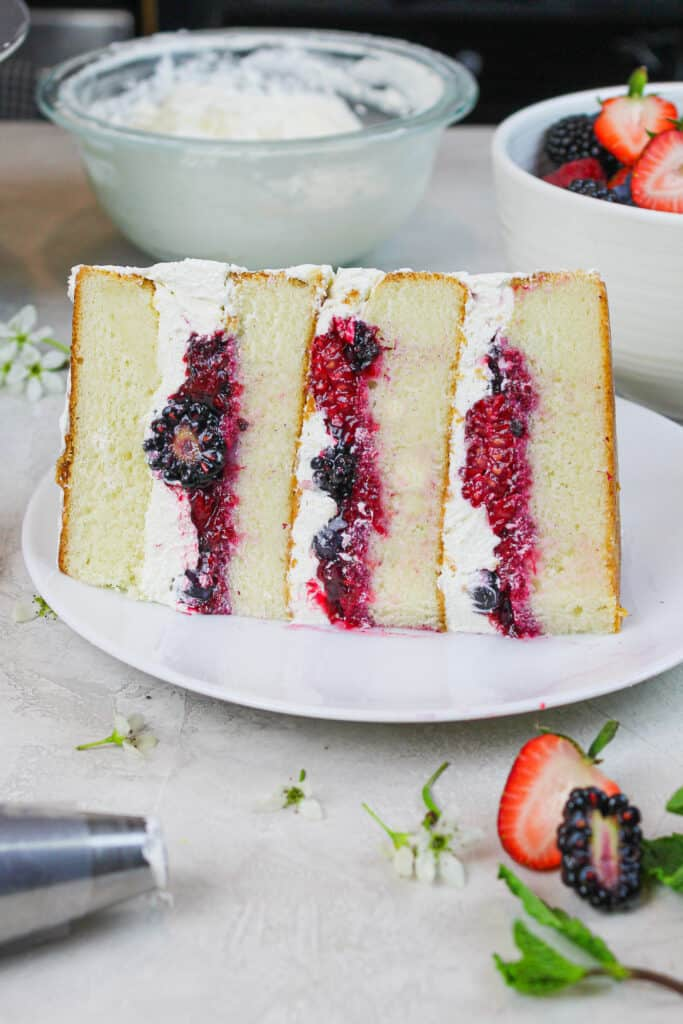 photo of a slice of berry chantilly cake showing mixed berry filling and fluffy mascarpone cream and soaked with blueberry simple syrup