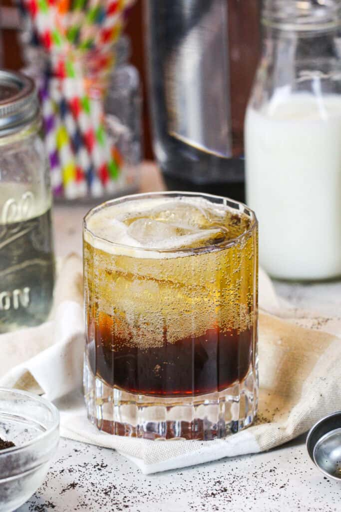 image of espresso soda in a pretty glass surrounded by the ingredients used to make it