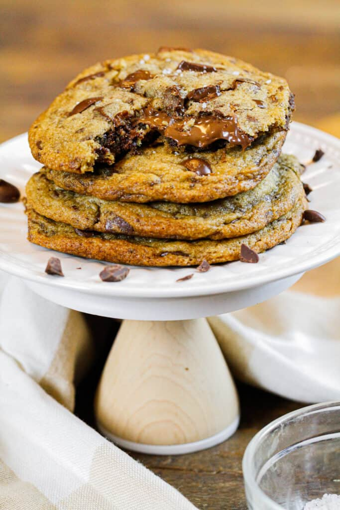 image of stack of brown butter nutella stuffed chocolate chip cookies, with the top cookie bitten into with nutella oozing out