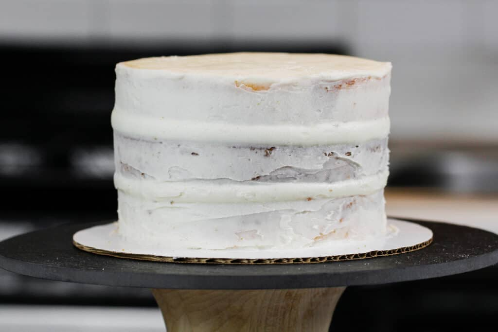 image of a layer cake with bulging sides, because air bubbles were trapped inside the frosting and as the cake settled the air pressed the frosting out.