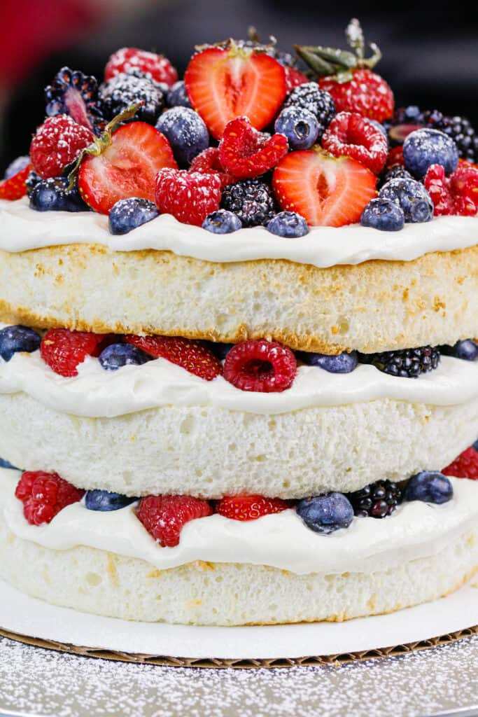 image of an angel food layer cake filled with loads of fresh berries and stabilized whipped cream
