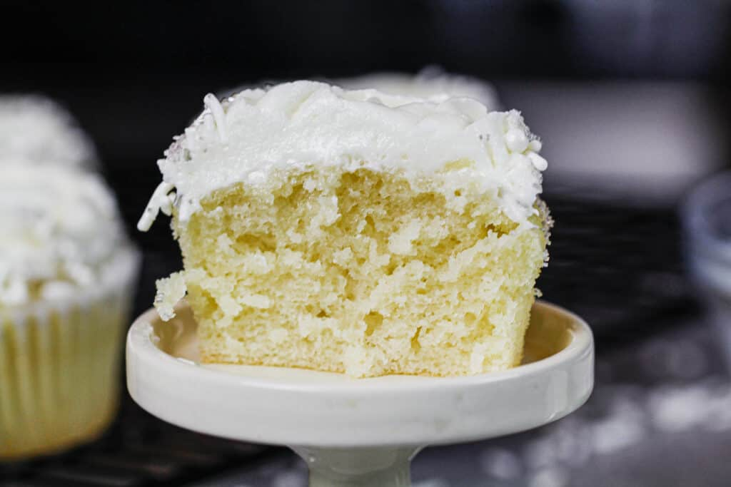 image of cut into almond cupcake, showing its fluffy and moist texture