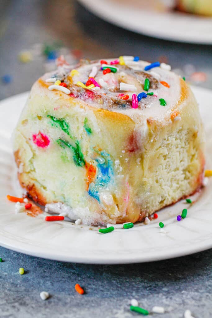 image of baked funfetti cinnamon roll on a plate, ready to be eaten