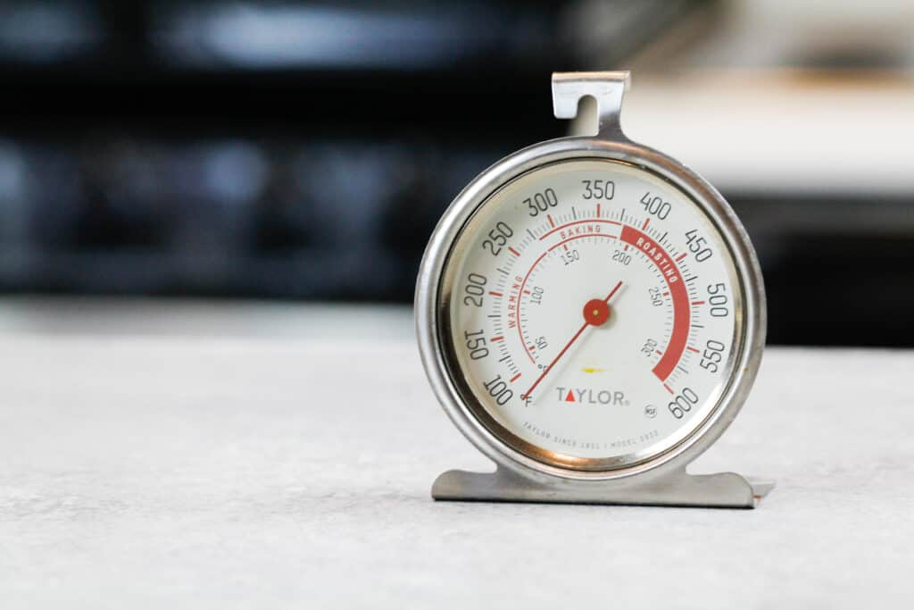 image of an oven thermometer being used to make sure an oven bakes accurately, to prevent cakes from sinking in the middle