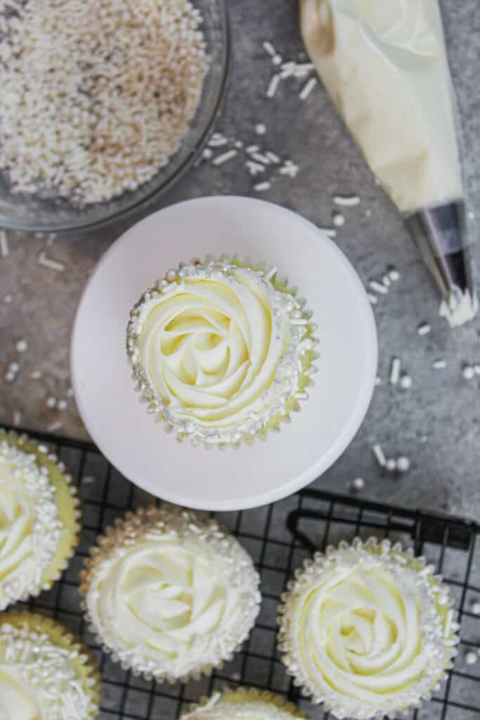 image of almond cupcakes decorated with a wilton 1m frosting tip and a fancy white sprinkle blend