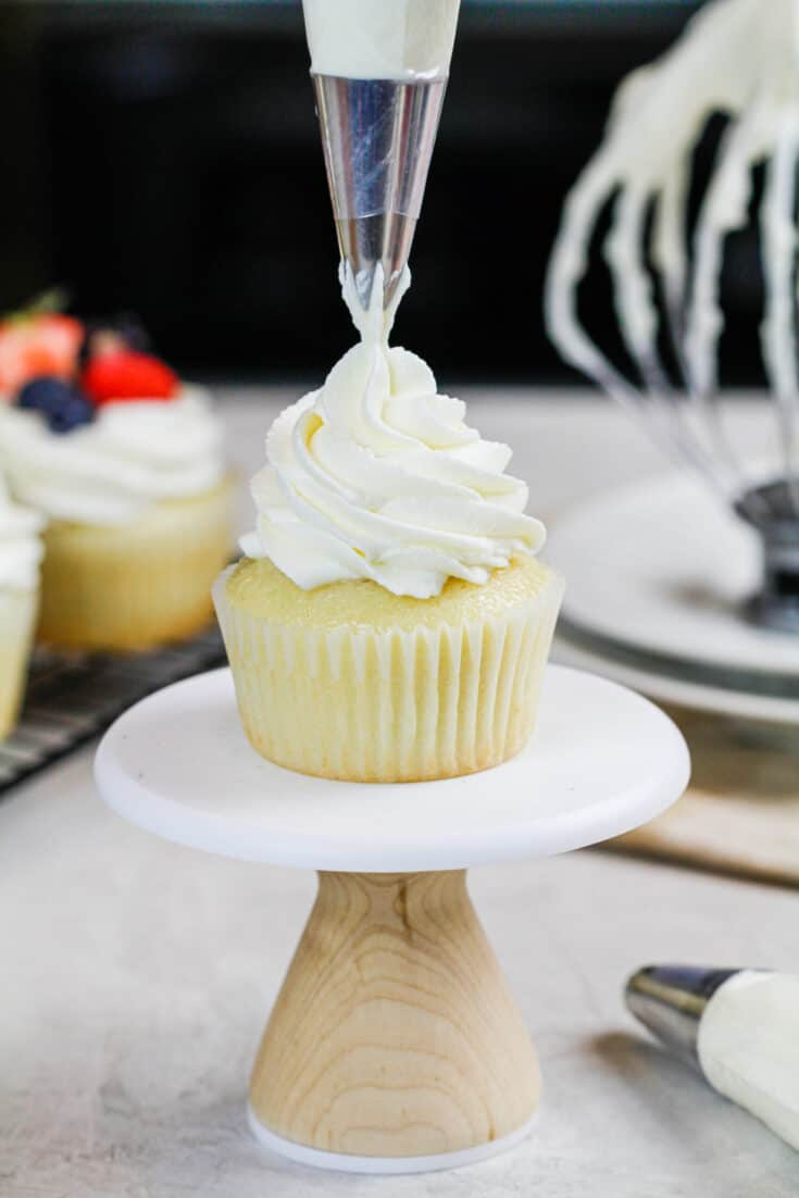 image of stabilized whipped cream frosting made with cream cheese being piped onto a cupcake
