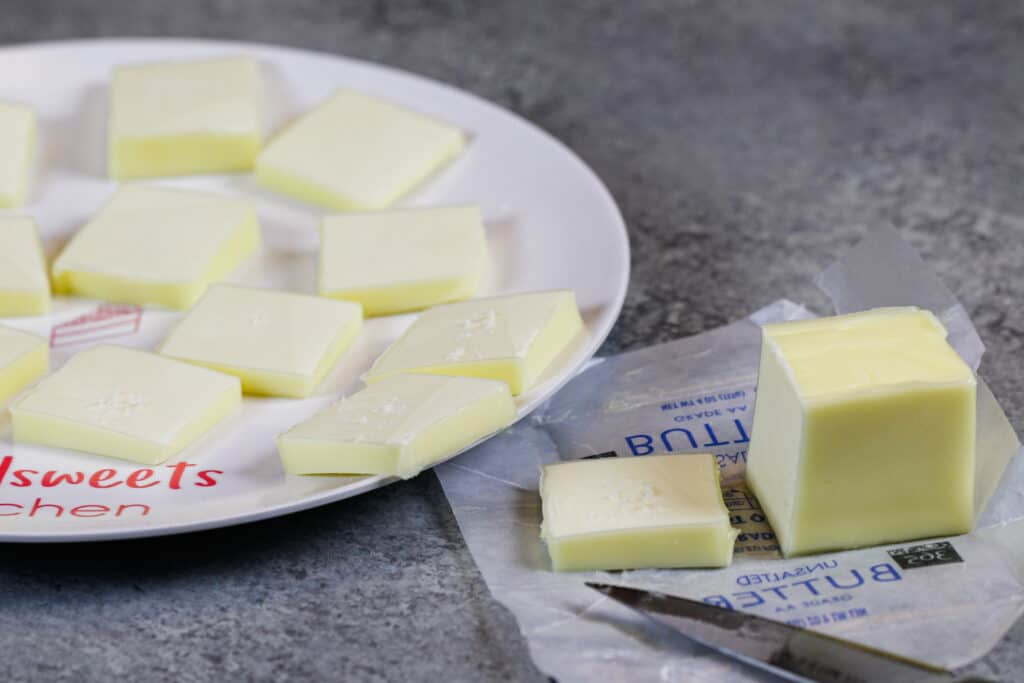 image of unsalted butter cut into small pieces to help it come to room temperature more quickly, shared as part of a baking substitutions guide with lots of substitutions for butter and oil