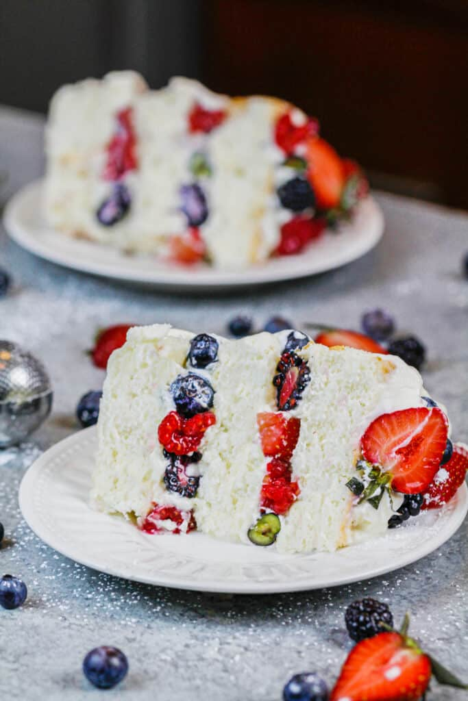 image of a slice of layered angel food cake filling with fresh berries and whipped cream frosting