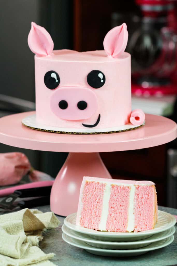 image of pig birthday cake with slice cut out to show pretty pink cake layers
