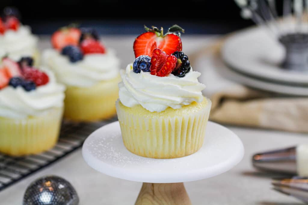 image of cupcakes topped with whipped cream frosting and fresh fruit