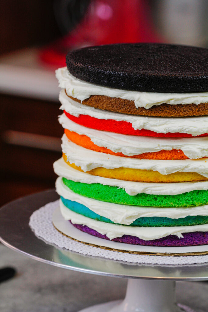 image of 8 color inclusive rainbow cake layers stacked and ready to be crumb coated for pride