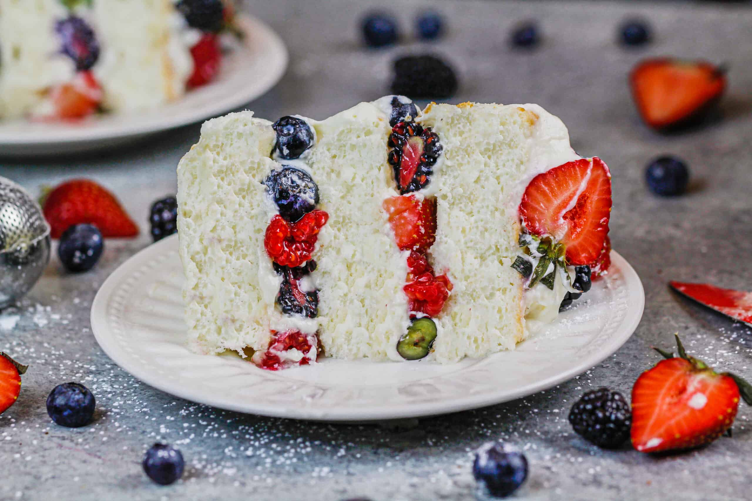 image of a slice of a layered angel food cake filled with berries and stabilized whipped cream
