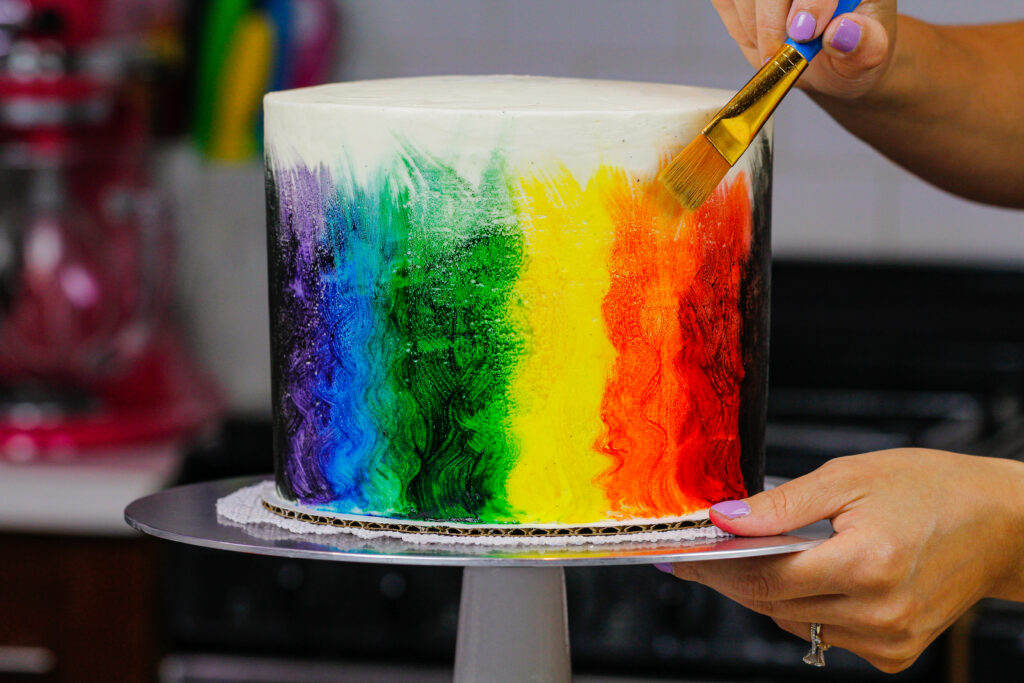 image of pride cake being painted rainbow colors with edible paint made from vodka and gel food coloring.