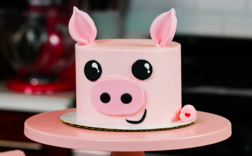 image of pig birthday cake on pink cake stand
