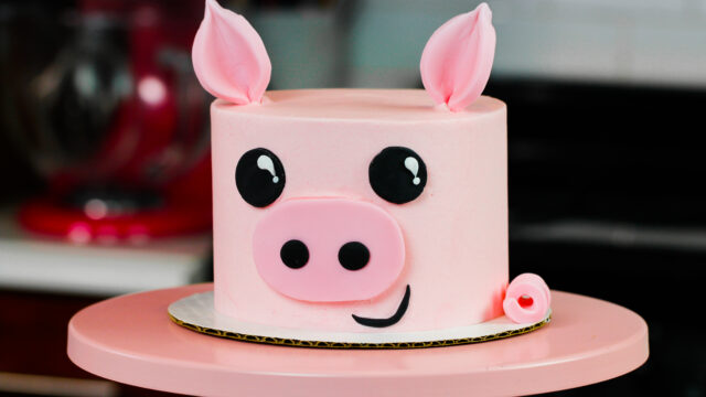 image of pig birthday cake on pink cake stand