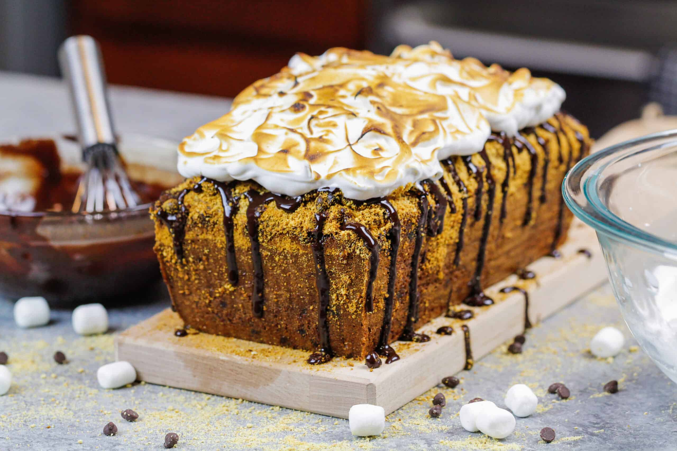 image of smores banana bread decorated with a chocolate drizzle and toasted marshmallow topping
