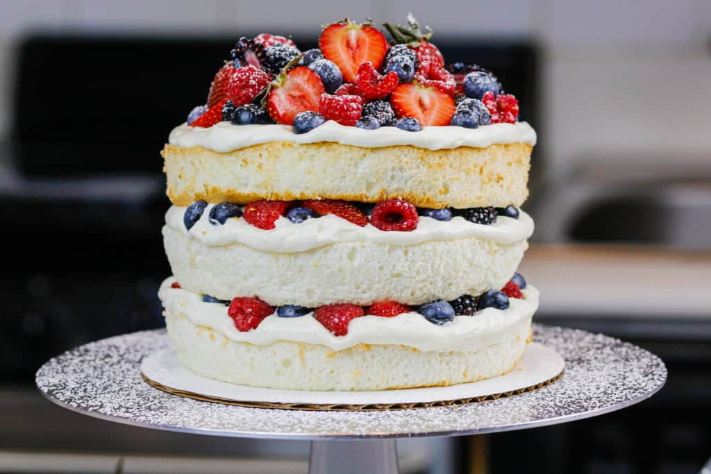 image of a layered angel food cake decorated with fresh berries and dusted with powdered sugar