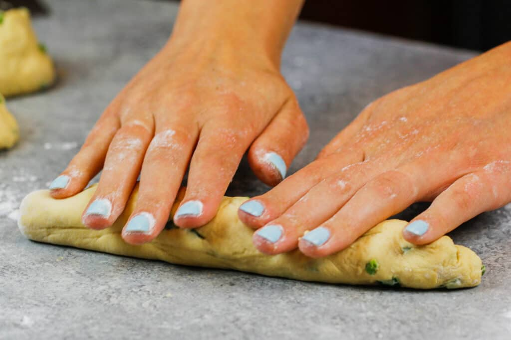 image of jalapeno cheddar bagels being rolled out to be formed into a bagel