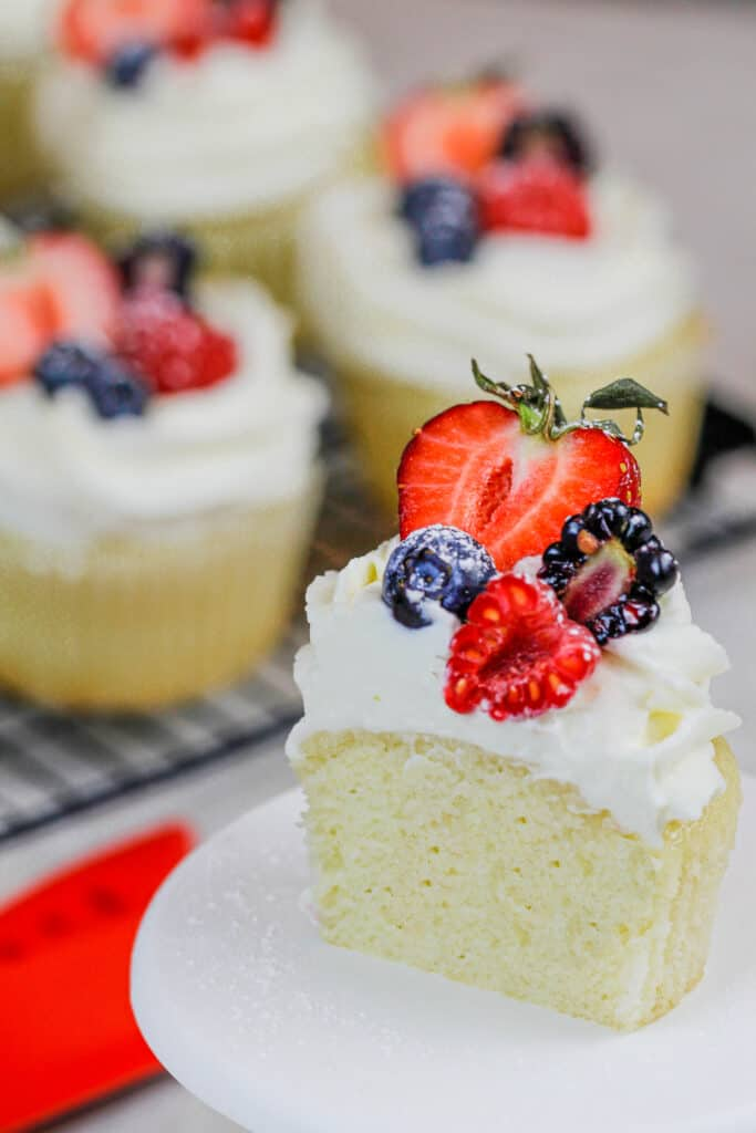image of a cupcake that's been cut into and topped with whipped cream frosting and fresh fruit