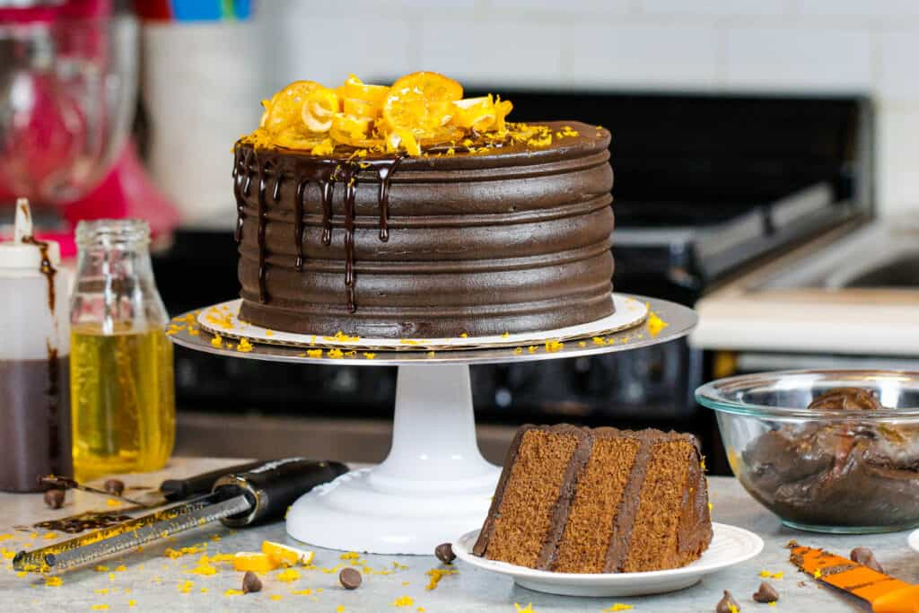 image of chocolate orange cake with slice in front on a plate showing how fluffy and tender the cake layers are