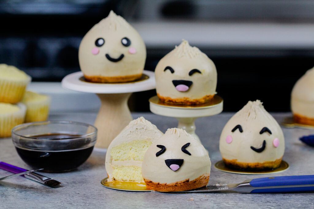 image of dumpling cupcakes with one cut open to show the moist vanilla cupcake it's made with