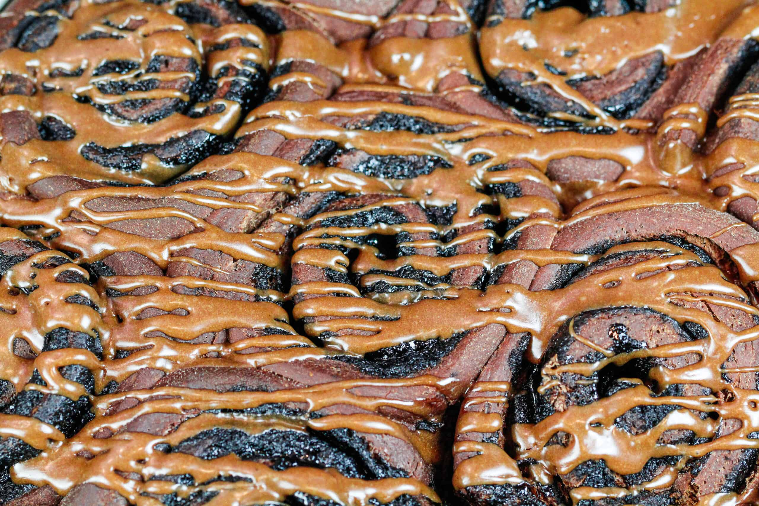 image of chocolate cinnamon rolls drizzled with a chocolate glaze