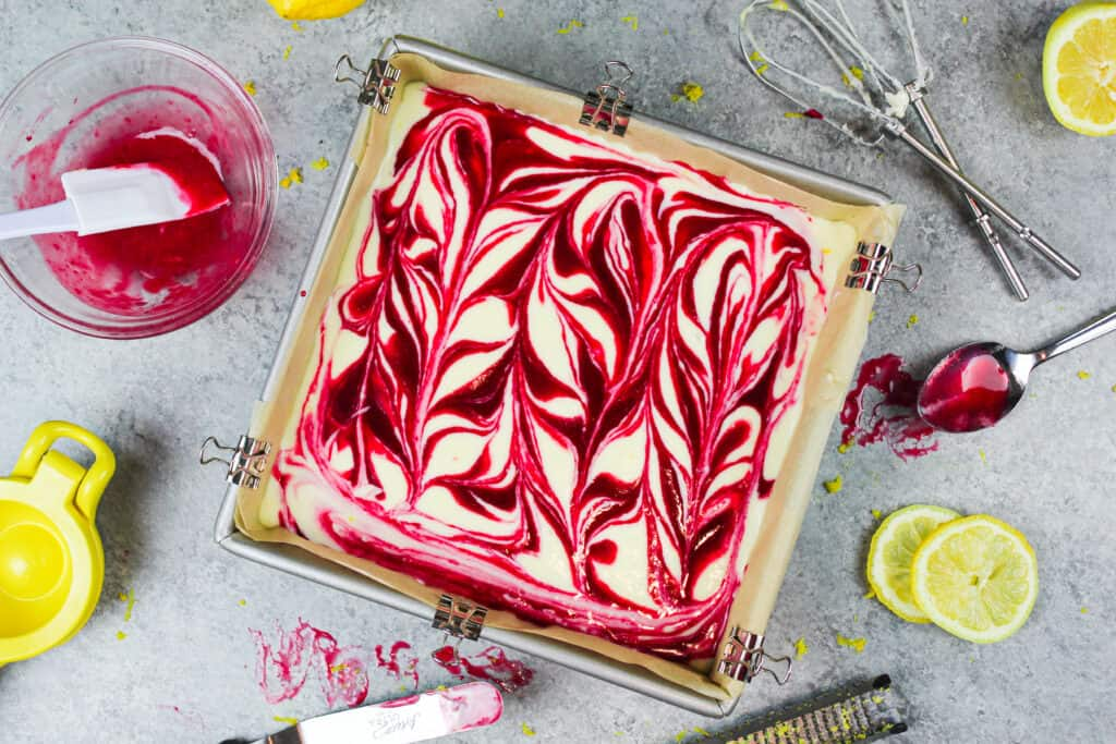 image of lemon raspberry cheesecake bars with a raspberry swirl in a pan ready to be baked
