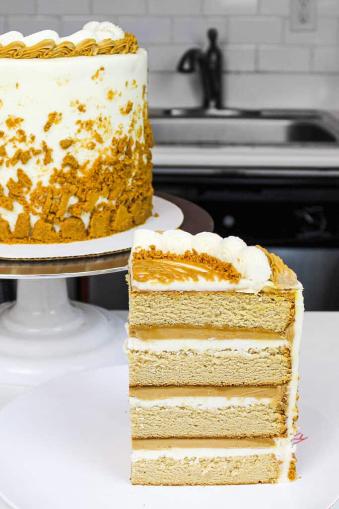 image of cookie butter cake slice on a plate showing it's cookie butter frosting and filling