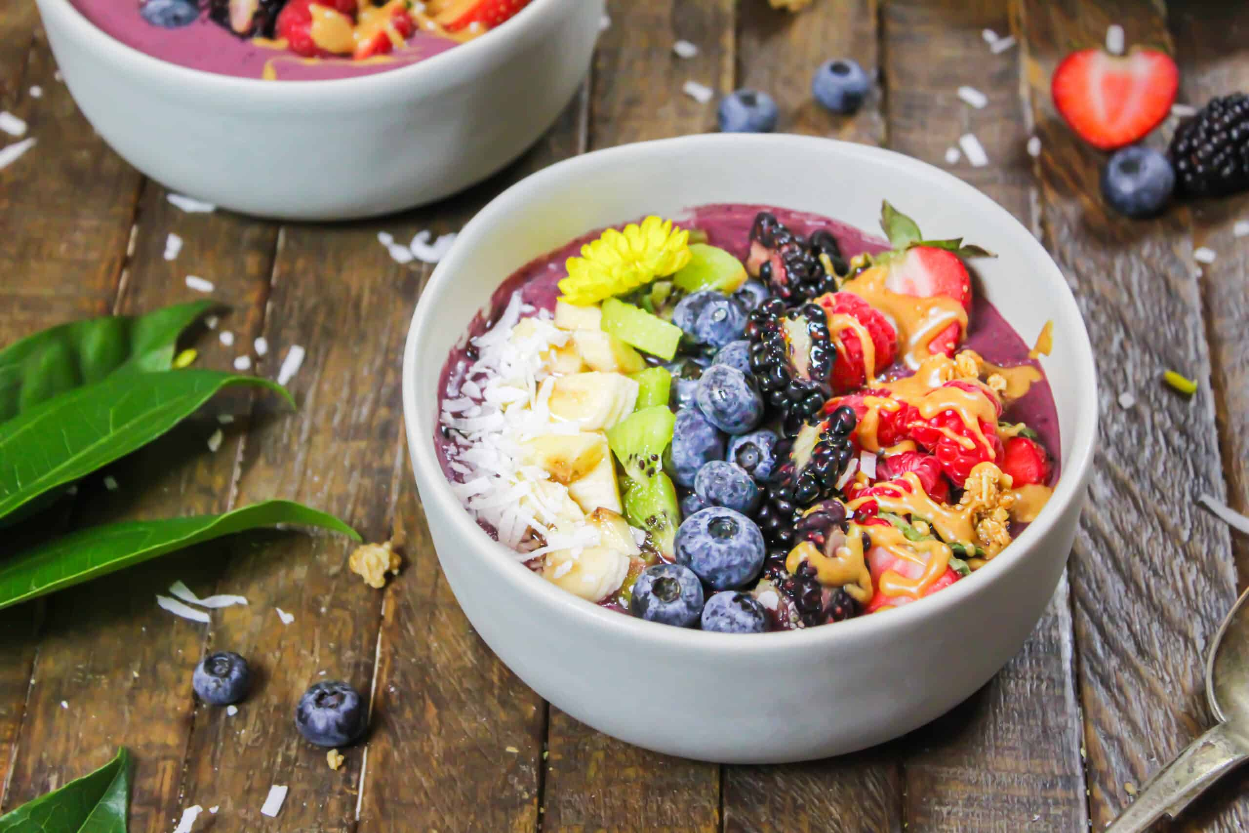 image of an acai bowl made with peanut butter and decorate with fresh fruit, granola, and some edible flowers