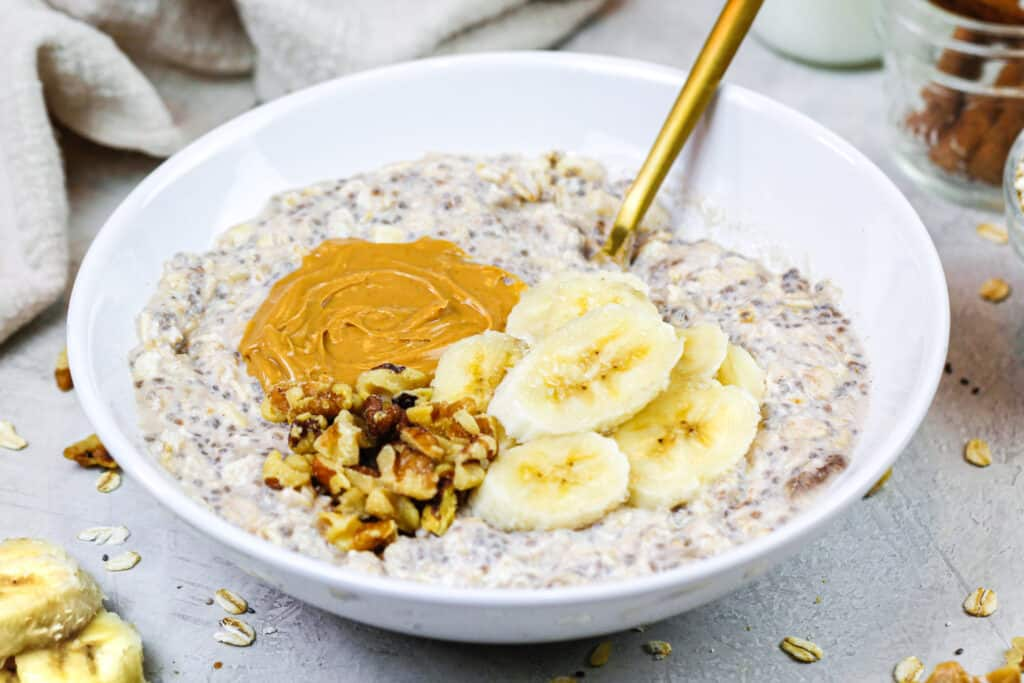 image of banana overnight oats in a bowl topped with peanut butter and chopped nuts
