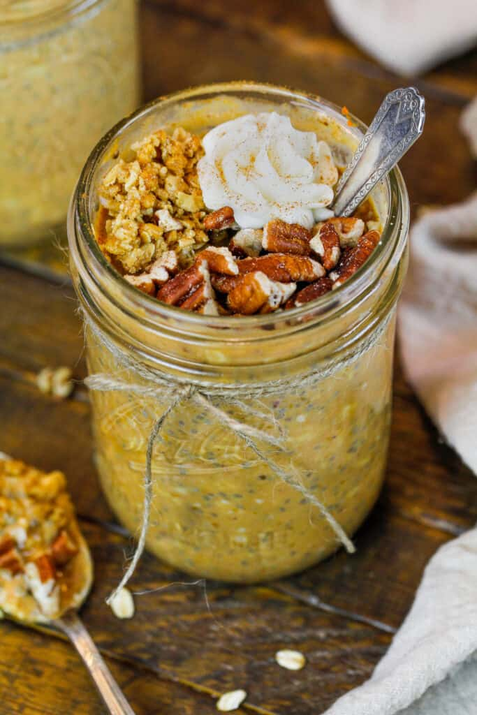 image of pumpkin spice overnight oats made in a mason jar and topped with nuts and granola