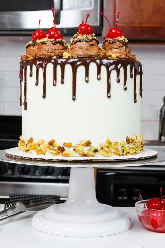 image of a rocky road cake made with fluffy chocolate cake layers, marshmallow frosting, and decorate with ice cream scoops and a chocolate drip