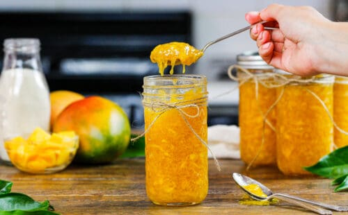 image of mango freezer jam being spooned out of a mason jar