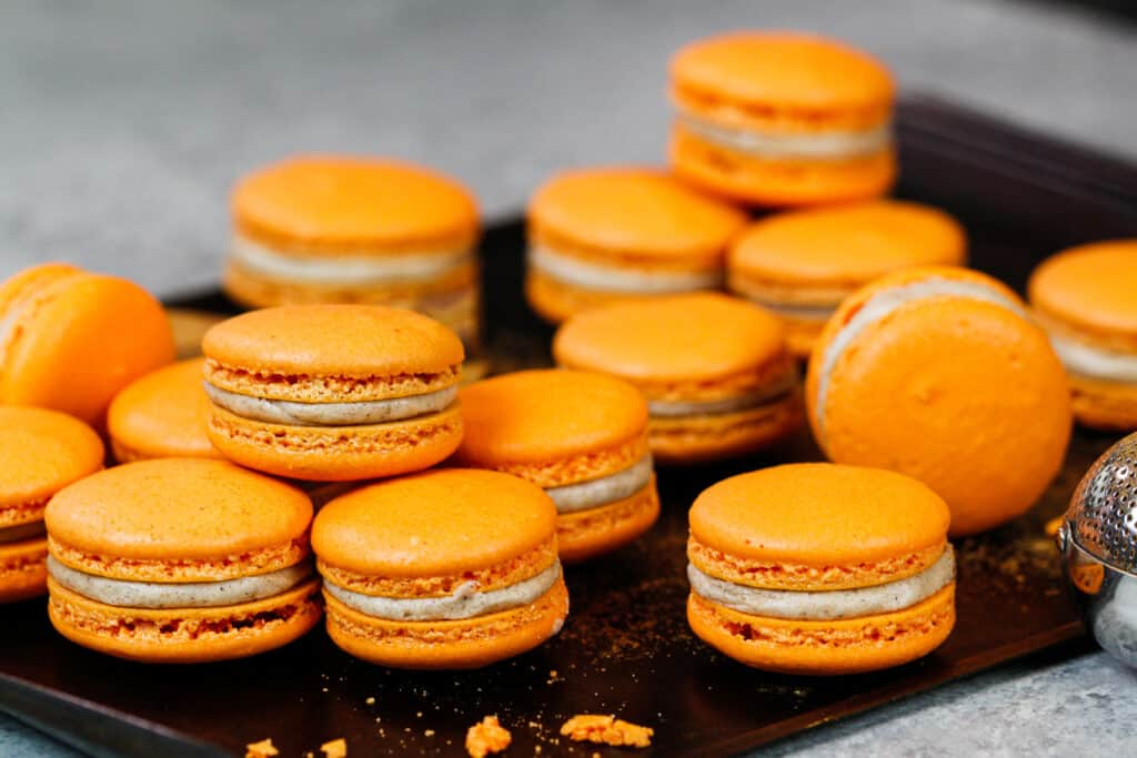 image of pumpkin macarons filled and resting on a tray before being eaten