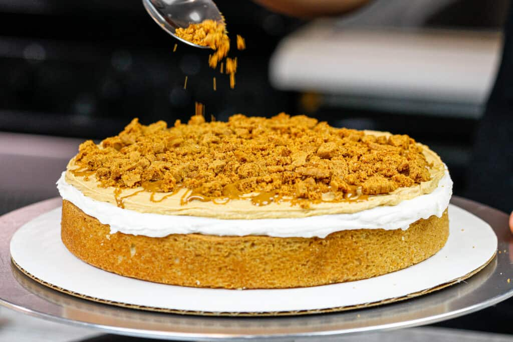 image of cookie butter cake being assembled with bits of biscoff cookies between each  layer