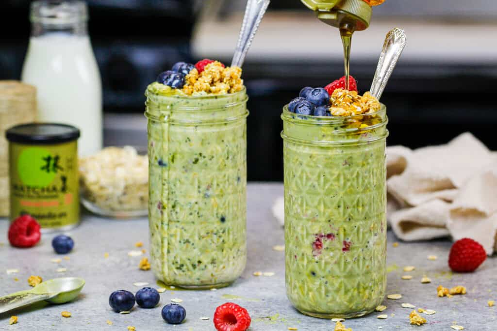 image of matcha overnight oats in cute mason jars topped with raspberries, blueberries and honey