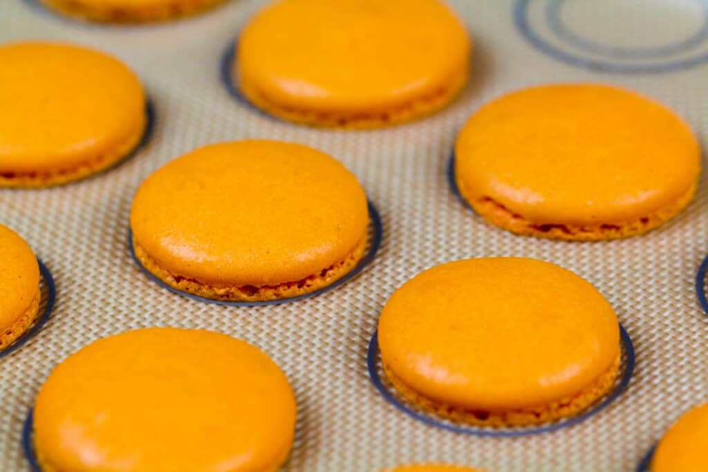 image of orange macaron shells baked on a silpat mat and cooling