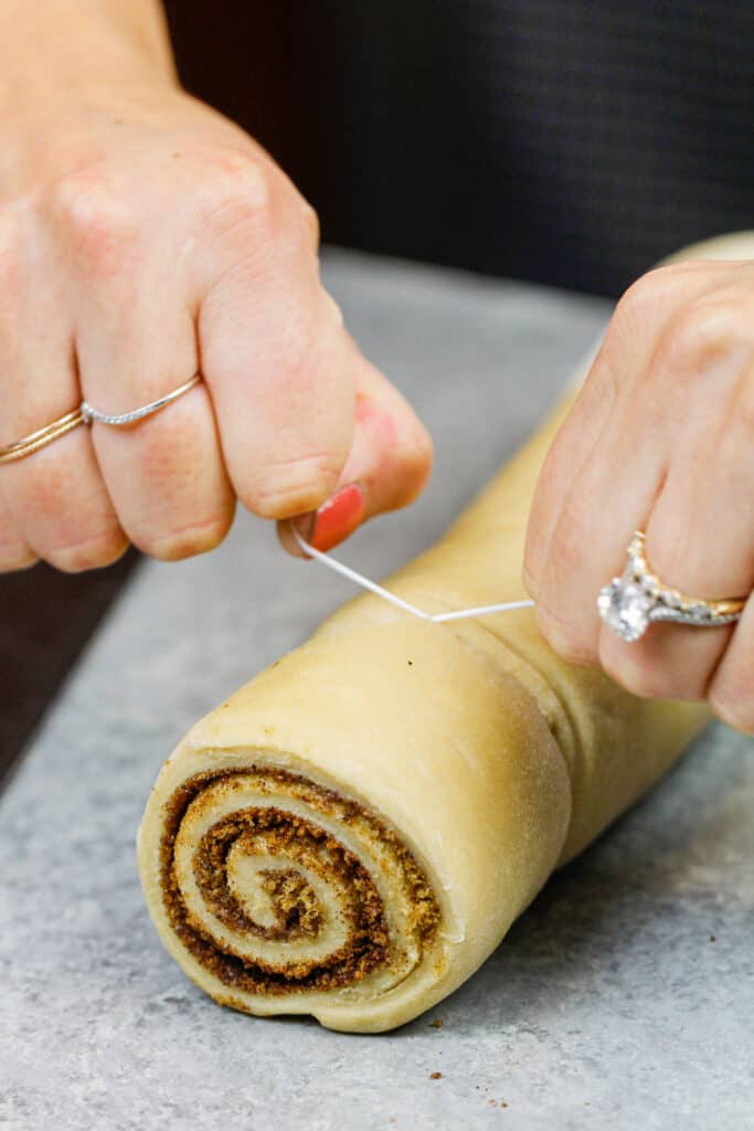 image of quick yeast cinnamon rolls being cut with dental floss